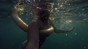 Smiling woman swimming and doing self-portrait. Young happy girl in the sea during summer vacation. Holiday concept stock footage