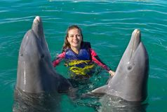 Smiling woman swimming with dolphins in blue water