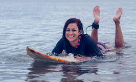Smiling woman swimming over surfboard in water Royalty Free Stock Photos