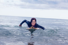 Smiling woman swimming over surfboard in water Stock Photos