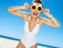 Smiling woman in swimsuit and funky pineapple glasses at beach. Heading to white sand blue sea paradise. Portrait of smiling woman in white swimsuit and funky Stock Photos