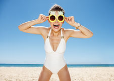 Smiling woman in swimsuit and funky pineapple glasses at beach. Heading to white sand blue sea paradise. Portrait of smiling woman in white swimsuit and funky Royalty Free Stock Photography