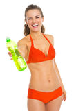 Smiling woman in swimsuit giving bottle of water Stock Photos