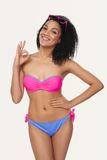 Smiling woman in swimsuit. Smiling happy mixed race african american - caucasian woman in bright swimsuit standing over gray background, gesturing OK sign Royalty Free Stock Images