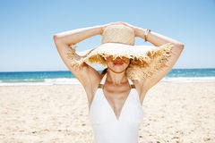 Smiling woman in swimsuit hiding under big straw hat at beach Stock Image
