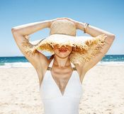 Smiling woman in swimsuit hiding under big straw hat at beach. Heading to white sand blue sea paradise. Smiling woman in white swimsuit hiding under big straw Royalty Free Stock Photos