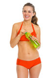 Smiling woman in swimsuit holding bottle of water Royalty Free Stock Photo