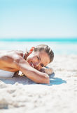 Smiling woman in swimsuit laying on sandy beach Royalty Free Stock Photos