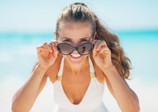 Smiling woman in swimsuit looking out from sunglasses on beach Stock Images