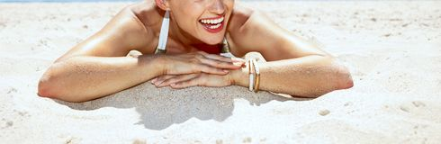 Smiling woman in swimsuit and pineapple glasses laying on beach. Heading to white sand blue sea paradise. Smiling woman in white swimsuit and funky pineapple Royalty Free Stock Photo