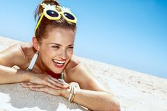 Smiling woman in swimsuit and pineapple glasses laying on beach. Heading to white sand blue sea paradise. Smiling woman in white swimsuit and funky pineapple Stock Photos