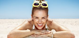 Smiling woman in swimsuit and pineapple glasses laying on beach. Heading to white sand blue sea paradise. Portrait of smiling woman in white swimsuit and funky Stock Photos