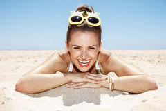 Smiling woman in swimsuit and pineapple glasses laying on beach. Heading to white sand blue sea paradise. Portrait of smiling woman in white swimsuit and funky Royalty Free Stock Images