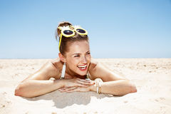 Smiling woman in swimsuit and pineapple glasses laying on beach. Heading to white sand blue sea paradise. Smiling woman in white swimsuit and funky pineapple Stock Image