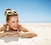 Smiling woman in swimsuit and pineapple glasses laying on beach. Heading to white sand blue sea paradise. Smiling woman in white swimsuit and funky pineapple Stock Photo