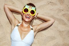 Smiling woman in swimsuit and pineapple glasses laying on sand. Warm sand treatment. Portrait of smiling woman in swimsuit and funny pineapple glasses laying on Royalty Free Stock Photography