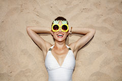 Smiling woman in swimsuit and pineapple glasses laying on sand Royalty Free Stock Photos