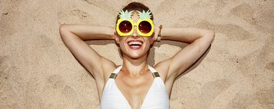 Smiling woman in swimsuit and pineapple glasses laying on sand. Warm sand treatment. Portrait of smiling woman in swimsuit and funny pineapple glasses laying on Stock Photos