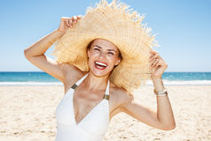 Smiling woman in swimsuit playing with big straw hat at beach. Heading to white sand blue sea paradise. Smiling woman in white swimsuit playing with big straw Royalty Free Stock Photography