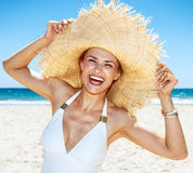 Smiling woman in swimsuit playing with big straw hat at beach. Heading to white sand blue sea paradise. Smiling woman in white swimsuit playing with big straw Royalty Free Stock Photos