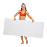 Smiling woman in swimsuit showing blank billboard Stock Images