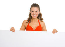 Smiling woman in swimsuit showing blank billboard. Smiling young woman in swimsuit showing blank billboard Royalty Free Stock Image
