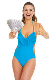 Smiling woman in swimsuit showing fan of dollars and thumb up Stock Images