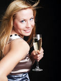 Smiling woman with sylvester champagne over dark. Smiling young woman with sylvester champagne over dark background Stock Photo