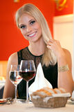 Smiling Woman at Table Having Bread and Wine. Royalty Free Stock Photo