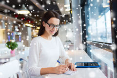 Smiling woman with tablet pc at cafe Royalty Free Stock Image