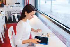Smiling woman with tablet pc and coffee at cafe Royalty Free Stock Photos