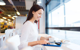 Smiling woman with tablet pc and coffee at cafe Stock Images