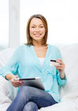 Smiling woman with tablet pc computer at home Royalty Free Stock Image