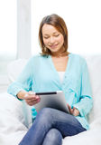 Smiling woman with tablet pc computer at home Royalty Free Stock Photos