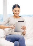 Smiling woman with tablet pc computer at home Royalty Free Stock Photo
