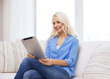 Smiling woman with tablet pc computer at home Stock Photos