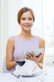 Smiling woman with tablet pc computer at resturant Royalty Free Stock Images