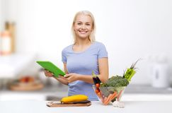 Smiling woman with tablet pc cooking vegetables Stock Photos