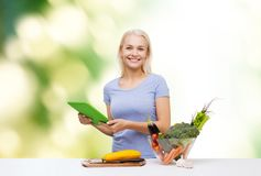 Smiling woman with tablet pc cooking vegetables Stock Photography