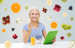 Smiling woman with tablet pc eating breakfast Stock Image