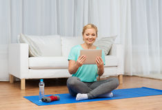 Smiling woman with tablet pc exercising at home Royalty Free Stock Photo