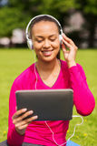 Smiling woman with tablet pc outdoors Stock Image