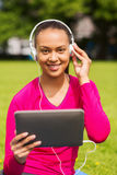 Smiling woman with tablet pc outdoors Stock Photo