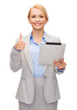Smiling woman with tablet pc showing thumbs up Stock Photo