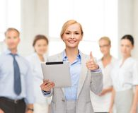 Smiling woman with tablet pc showing thumbs up Royalty Free Stock Photo
