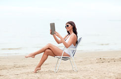 Smiling woman with tablet pc sunbathing on beach Royalty Free Stock Image
