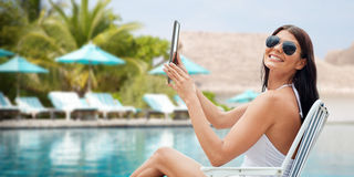 Smiling woman with tablet pc sunbathing on beach Royalty Free Stock Photo