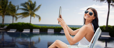 Smiling woman with tablet pc sunbathing on beach Stock Photography