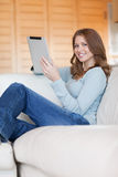 Smiling woman with tablet relaxing on sofa Stock Images