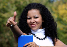 Smiling woman with a tablet showing thumb up, outdoor. Stock Photos